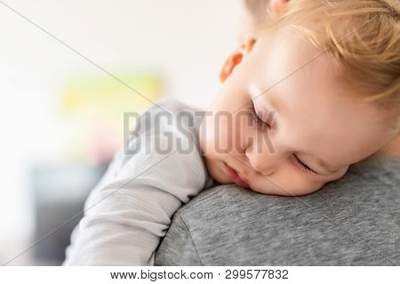 Close-up portrait of cute adorable blond caucasian toddler boy sleeping on fathers shoulder indoors. Sweet little child feeling safety daddys hand. Responsibility and childcare. happy childhood poster