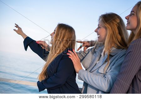 Three Beautiful Teenage Friends Girls Having Fun Near The Sea. Pointing Somewhere Far Away With A Fi