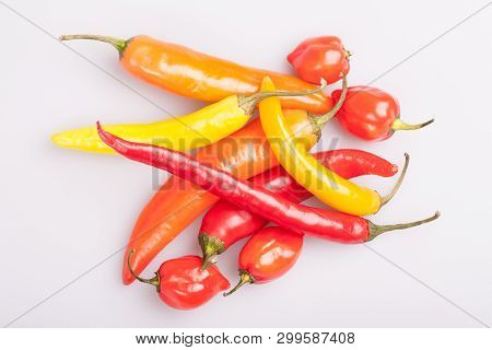 Heap Of Various Chili Peppers Isolated On White Background. Cooking Ingredients, Spicey Taste And Or