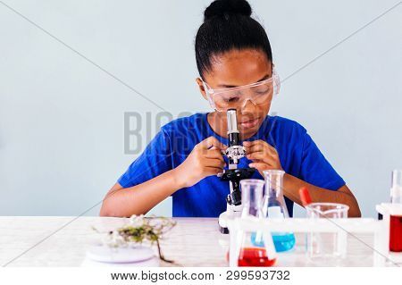Young African American Kid Using Microscope And Experimenting Scientific Lab Along With Chemical Sub