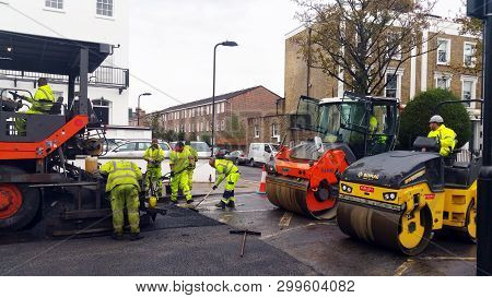 London, UK - November 01, 2018: Workers resurface by laying asphalt on a street in London, UK