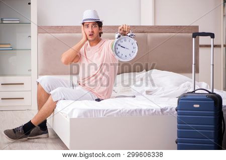 Man with suitcase in bedroom waiting for trip