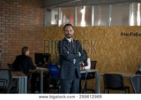 Businessman In Suit Standing Middle Office With Crossed Hands. Colleagues On Background. Business Co