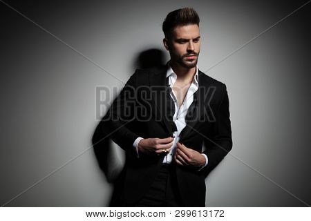elegant man in black tuxedo buttoning his suit on gray studio background