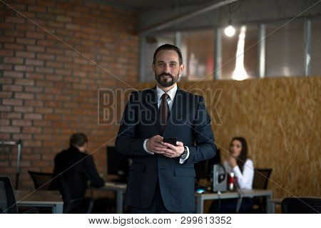 Young Beardy Businessman Holding Phone While Standing Middle Office. Having Colleagues On Background