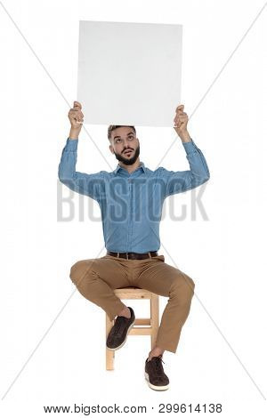 seated goofy man in blue jeans shirt holds a blank billboard up in the air on white background