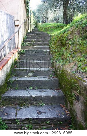 Old Steep Stairway Uphill In Rock, Long Endless. Path That Runs Along The Gardens