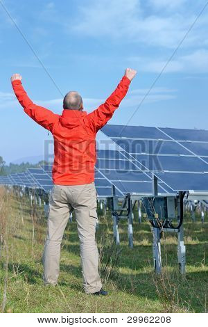 Male engineer at work place, solar panels plant industy in background poster