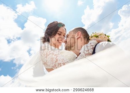 Loving Couple Of Newlyweds Walks In The City And A Veil Flying In The Wind On Blue Sky Background