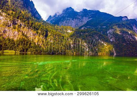 Transparent clear water of a mountain lake Königssee. Bavaria, Germany. Journey to the magic. The lake is surrounded by high mountains. The concept of active, ecological and photo tourism