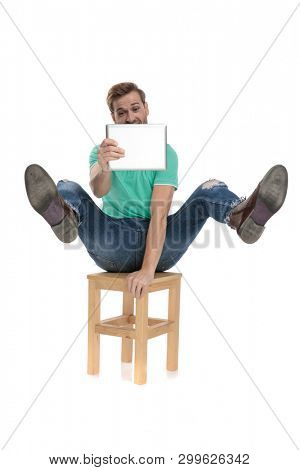 seated goofy man in green polo shirt falling from chair with tablet in hand and legs up in the air on white background