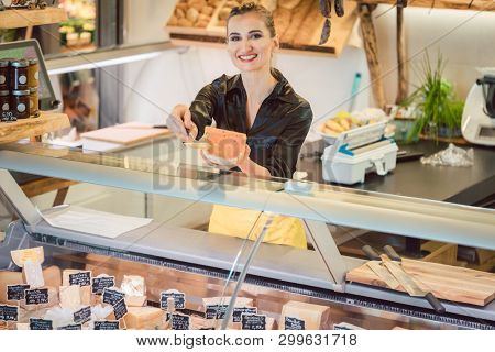 Beautiful woman offering cheese on delicatessen counter cutting a test bit off