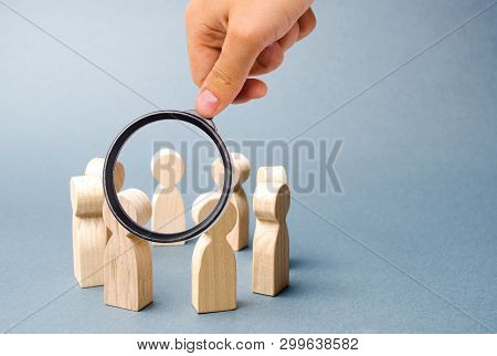 Magnifying Glass Is Looking At People Stand In A Circle On A Gray Background. Wooden Figures Of Peop