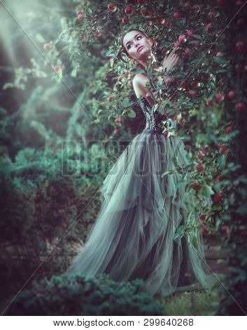 Beauty romantic model girl fashion posing in garden trees, enjoying nature in apple orchard. Beautiful brunette young woman in fantasy Garden, long dress. Outdoor full length portrait. Fairy tail
