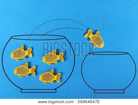 Yellow fish jumping out of water in fishbowl