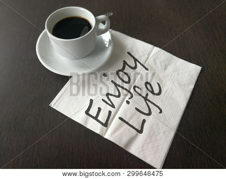 Black coffee and white napkin with hand written enjoy life