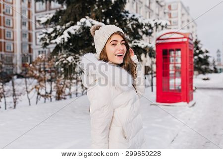 Glad Caucasian Woman In Knitted Hat Goes To Red Phone Booth In Winter Day. Outdoor Portrait Of Attra