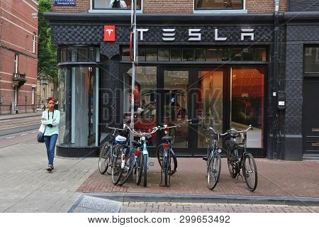 Amsterdam, Netherlands - July 10, 2017: People Visit Tesla Car Dealership In Amsterdam. Pieter Corne