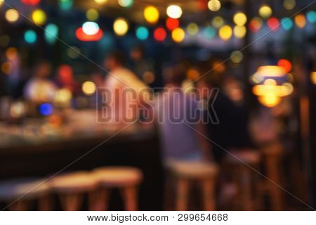 Blurred Background Of People Sitting At Restaurant, Bar Or Night Club With Colorful Lights Bokeh. Ab