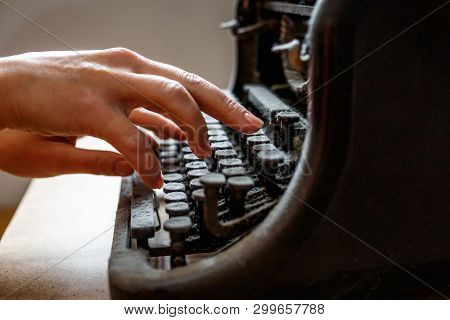 Woman Hands Type On An Old Vintage Dust-covered Typewriter