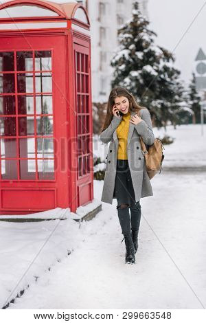 Full-length Portrait Of Busy Smiling Woman Talking On Smartphone, Walks By Call-box. Outdoor Photo O