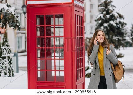 Refined Caucasian Female Model Laughing Near Red Phone Booth In Winter Morning. Outdoor Portrait Of