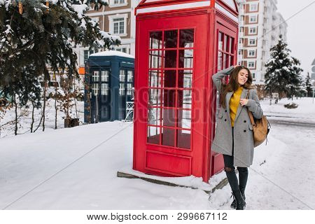 Full-length Portrait Of Magnificent Young Woman In Stylish Coat Posing With Pleasure Near British Ph