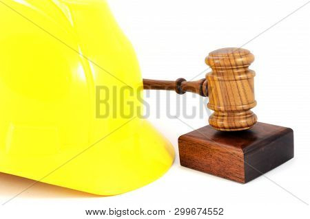 A Yellow Hardhat And Wooden Gavel For Labour Law Concepts And Legalities In The Workplace Of A Const