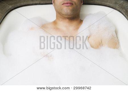 Man soaking in bubble bath