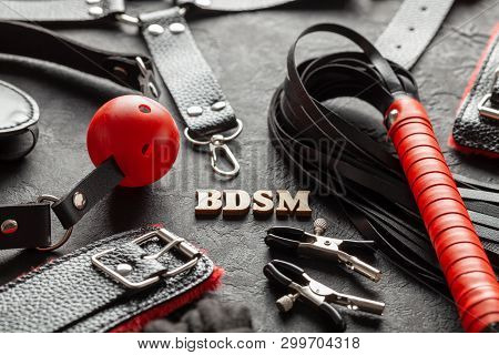 Bdsm Sex Toys For Adults. On Black Background Whip, Gag, Handcuffs And Leather Straps.