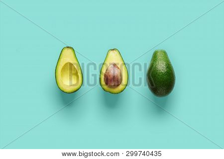 Whole Avocado Fruit And Two Halves In A Row Isolated On Blue Background