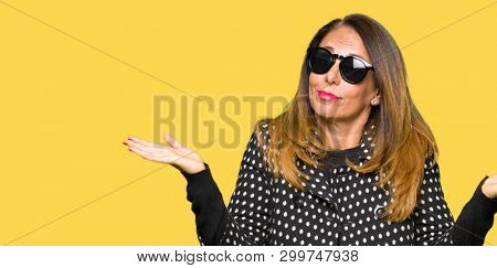 Beautiful middle age woman wearing sunglasses clueless and confused expression with arms and hands raised. Doubt concept.