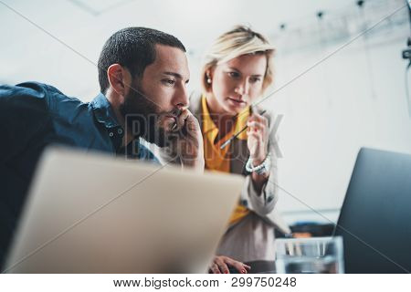 Closeup View Of Two Young Coworkers Working On Mobile Laptop Computer At Office.woman Pointing On To