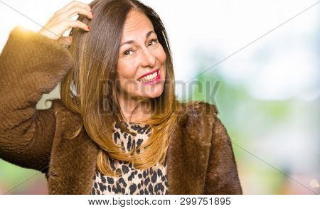 Beautiful middle age elegant woman wearing mink coat confuse and wonder about question. Uncertain with doubt, thinking with hand on head. Pensive concept.