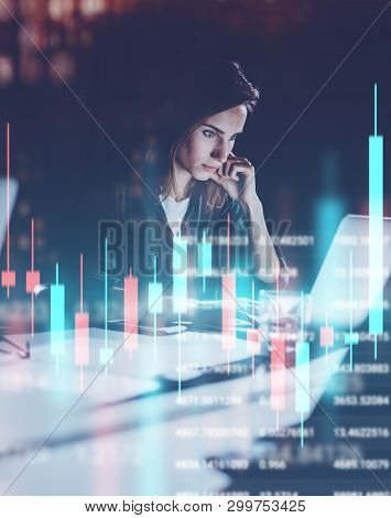 Young Woman Working At Night Modern Office Loft.red And Green Candlestick Chart And Stock Trading On