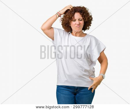 Beautiful middle ager senior woman wearing white t-shirt over isolated background confuse and wonder about question. Uncertain with doubt, thinking with hand on head. Pensive concept.