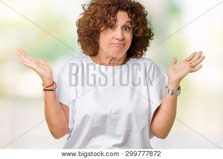 Beautiful middle ager senior woman wearing white t-shirt over isolated background clueless and confused expression with arms and hands raised. Doubt concept.