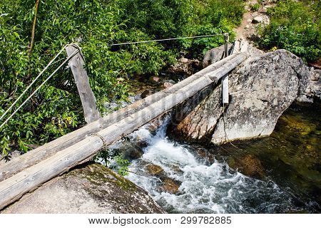 Old Wooden Tourist Bridge Made Of Woods And Ropes Across Mountain River.