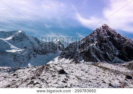 Dawn Or Sunset In Mountains In Winter. Mountain Range Under Pink Clouds. Rocks Are Covered With Snow
