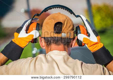 Worker Wearing Noise Reduction Ear Muffs. Loud Noises Job.