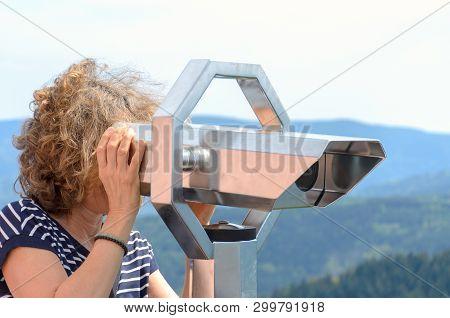 Woman Tourist Looking Through A Binocular Telescope From A Vantage Point In Mountainous Terrain