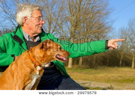Elderly man hunting with dog in nature poster