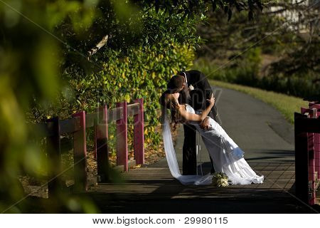 Groom Holding Wife And Kissing On A Bridge