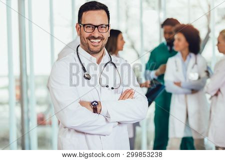 Male Doctor With Colleagues In Background, Doctor Looking At Camera With Emergency Team In Backgroun