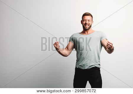 Happy successful handsome man on white wall background. Casual portrait.