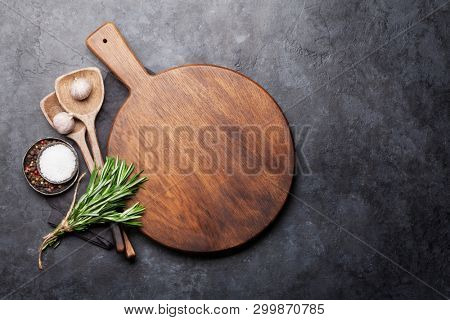 Cooking ingredients and utensils on stone table. Top view with cutting board for copy space