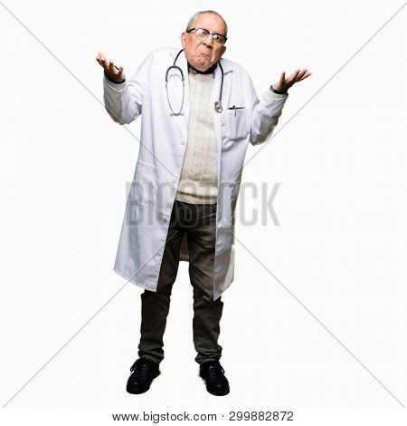 Handsome senior doctor man wearing medical coat clueless and confused expression with arms and hands raised. Doubt concept.