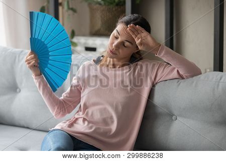 Woman Feels Discomfort From Heat Waving Blue Fan To Cool