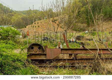 Discarded conveyor belt motor with chain sprocket laying in tall weeds. poster