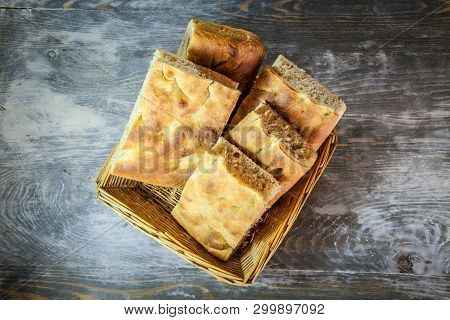 Italian Bread Of Focaccia Genovese Type On A Rustic Wooden Table, Sliced In Two Squared Pieces. The